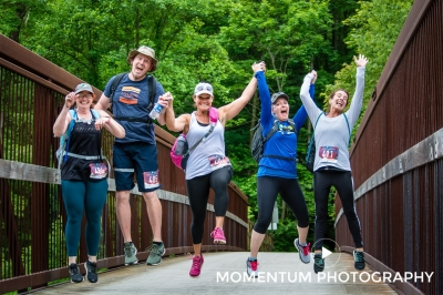 Participants of the 50K Ghost Town Trail Challenge leap for joy after completing 13 miles of the 32 mile run/hike challenge. Photo by Lance Harshbarger.