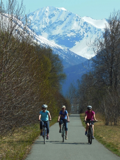 Bicyclists enoying spring sunshine on the Bird-to-Gird Trail near Anchorage. Photo by Susan Sommer.