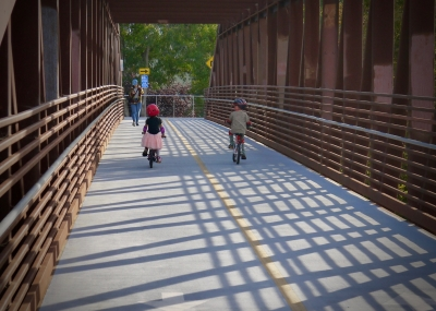 Two young trail users crossing the River Oaks Pedestrian Bridge along the Guadalupe River Trail. Photo by Yves Zsutty.