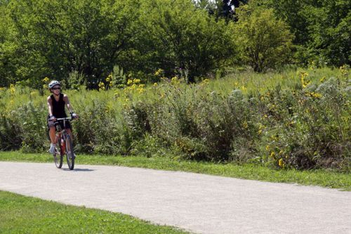 photo: A bicyclist along the crushed limestone surface of Springbrook Prairie Trail
