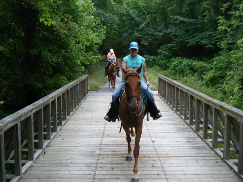 photo: Horseback riders crossing bridge. Photo by Kari Kirby.