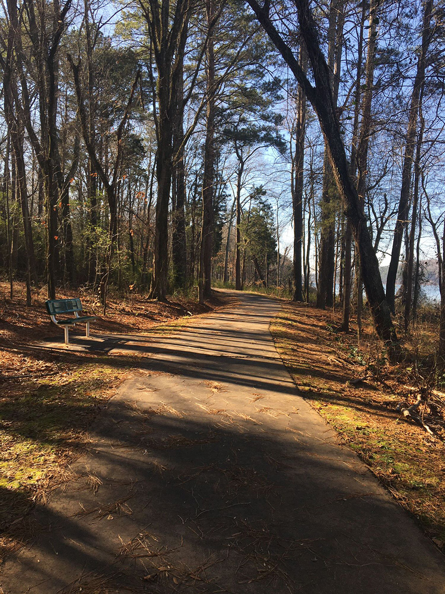photo: Trail passes through woods and along lake with rest stops. Photo by Donna Kridelbaugh.