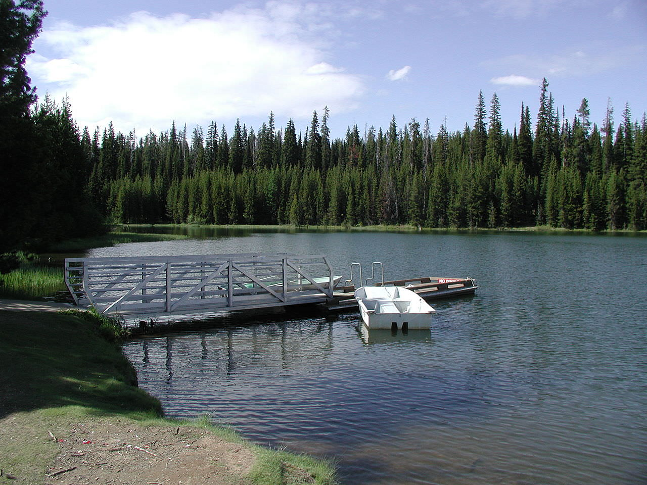 photo: A metal and wooden dock and a small white boat floating beside in shallow water. Photo by USFS.